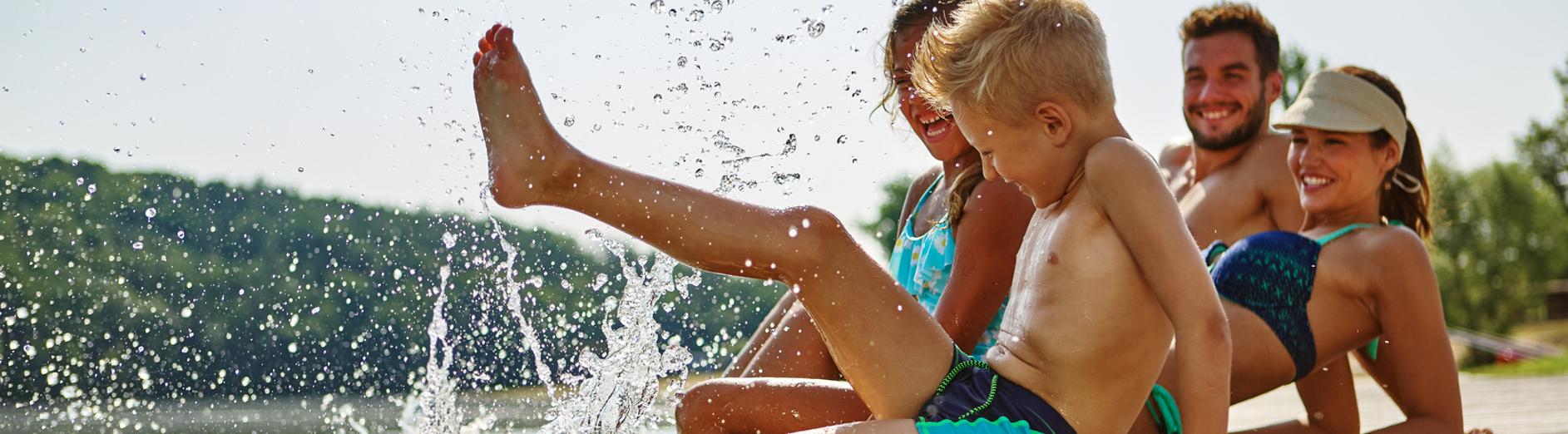 Familie am See badet glücklich mit Füßen im Wasser im Sommer