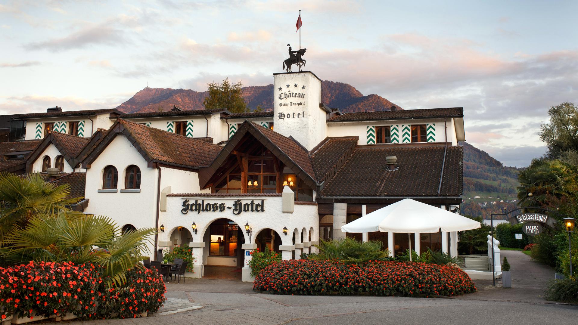 Schloss-Hotel im Swiss-Chalet Merlischachen Totalansicht abends mit Geranienbepflanzung