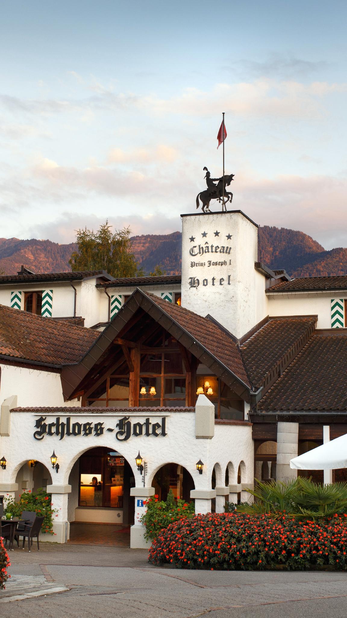 Schloss-Hotel im Swiss-Chalet Merlischachen bei Abendstimmung mit Geranien