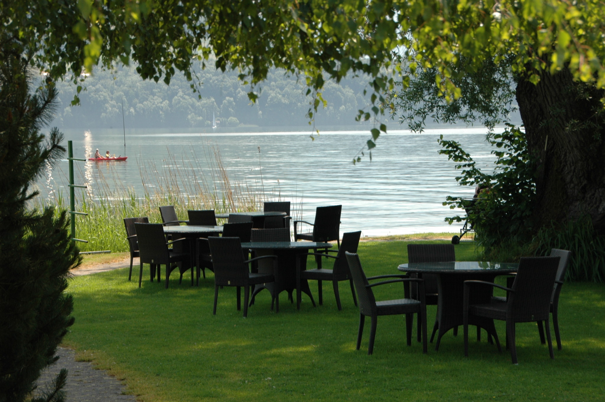 Schloss-Park mit Tischen und Sicht auf den See