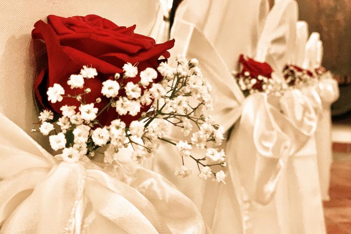 Stuhldekoration mit roter Rose und weisem Satin im Swiss-Chalet Merlischachen für eine Hochzeit